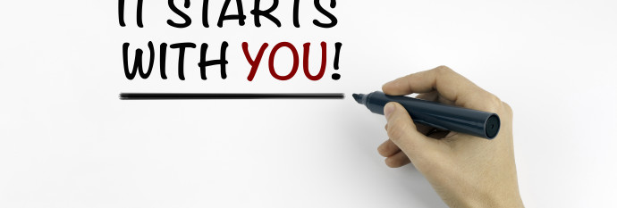 Hand with marker writing: It Starts With You!